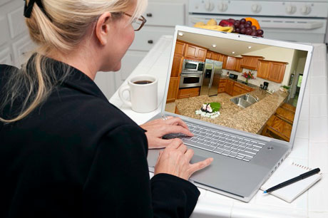 Woman In Kitchen Using Laptop to Research Home Improvement Ideas.