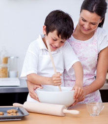 Adorable little boy preparing cookies with her mother