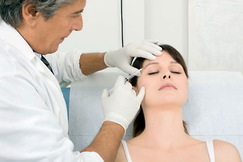 Caucasian woman receiving an injection of botox from a doctor