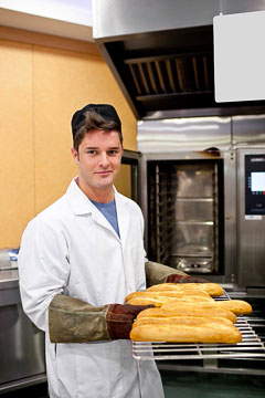 Happy baker showing his baguettes
